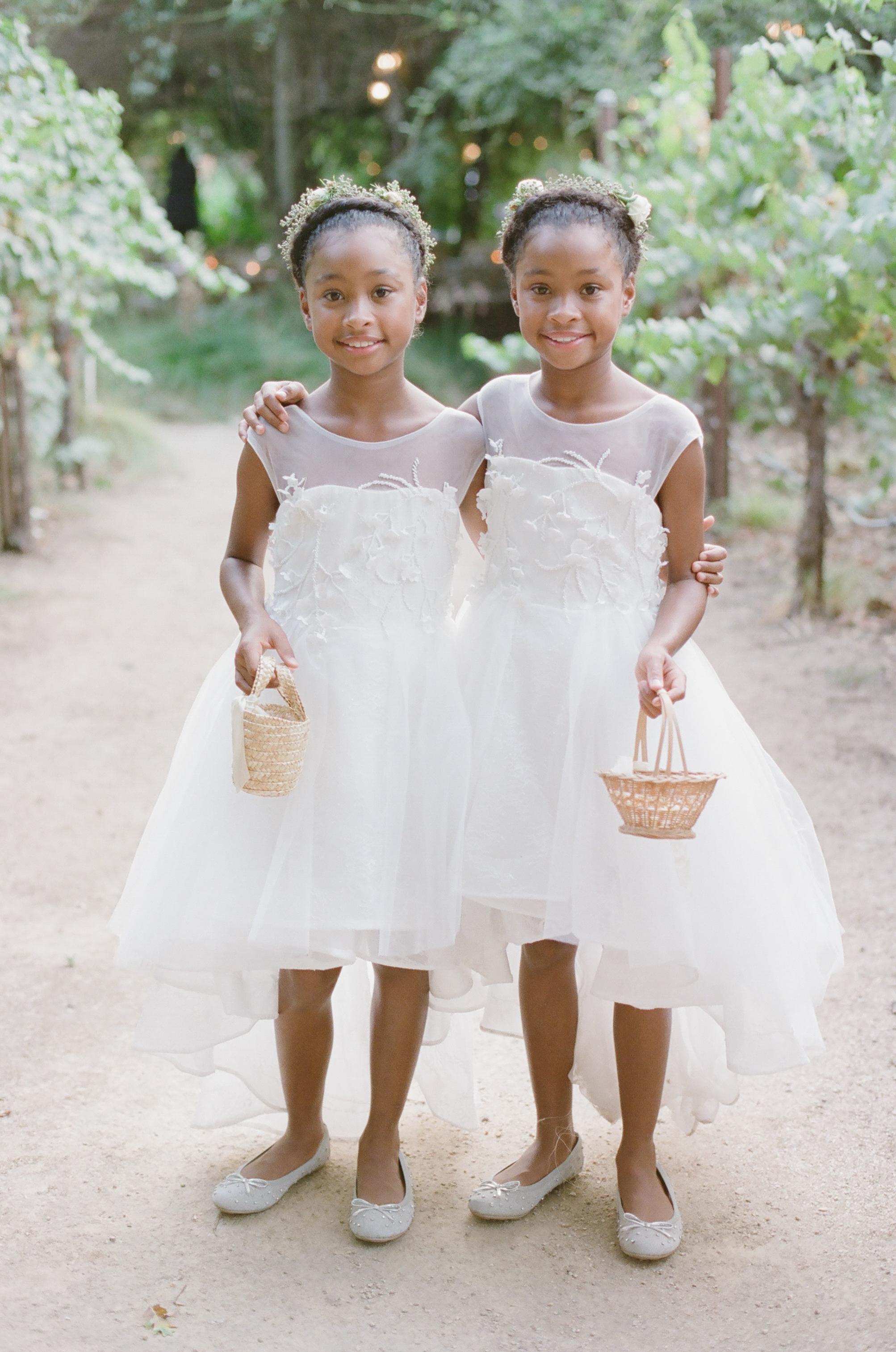 two flower girls holding small wicker baskets