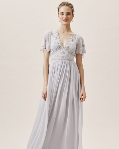 long flowing gray blue dress with plunging neckline scalloped sleeves and beaded bodice