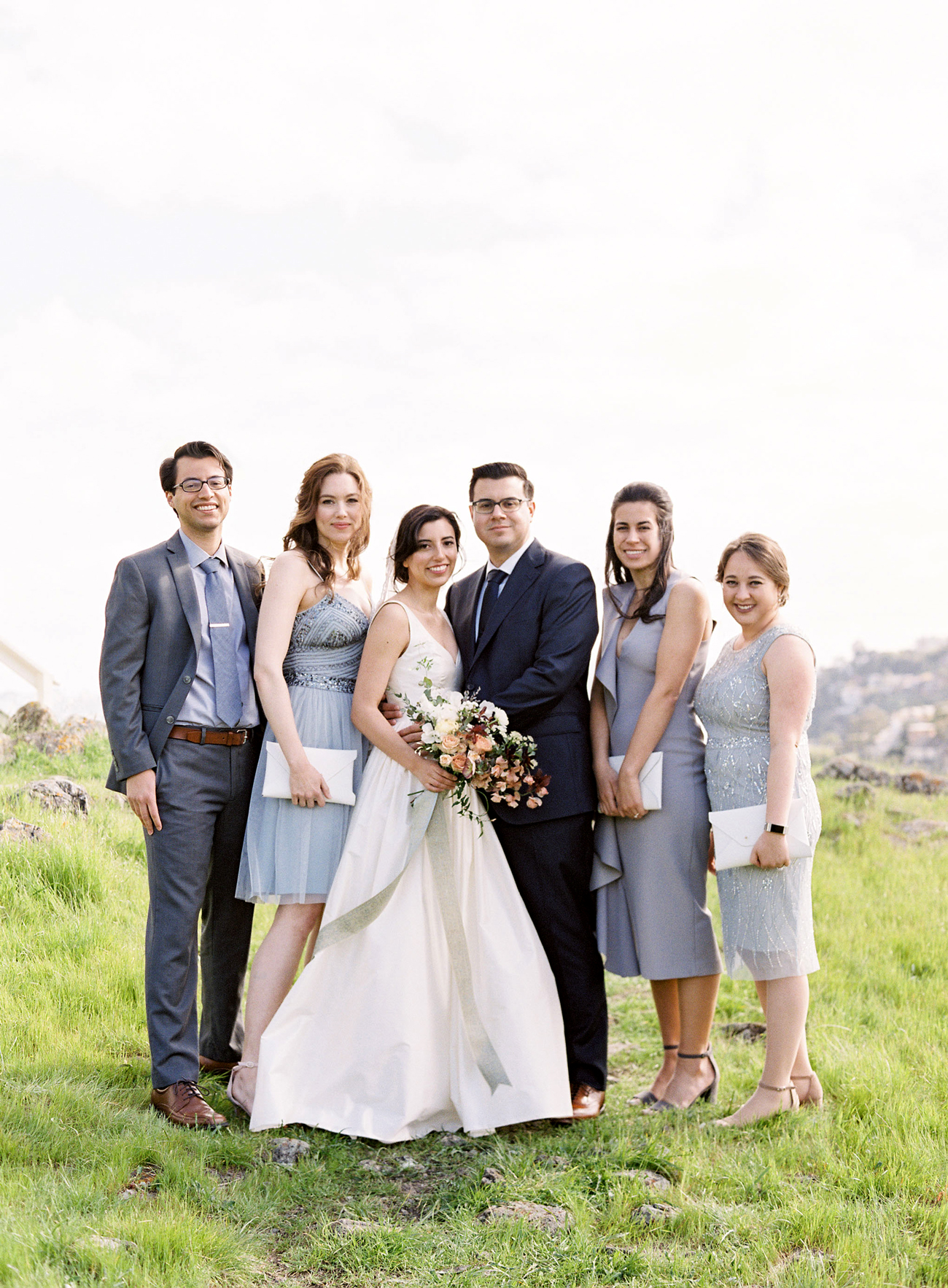 bride and groom with small wedding party on grassy hillside