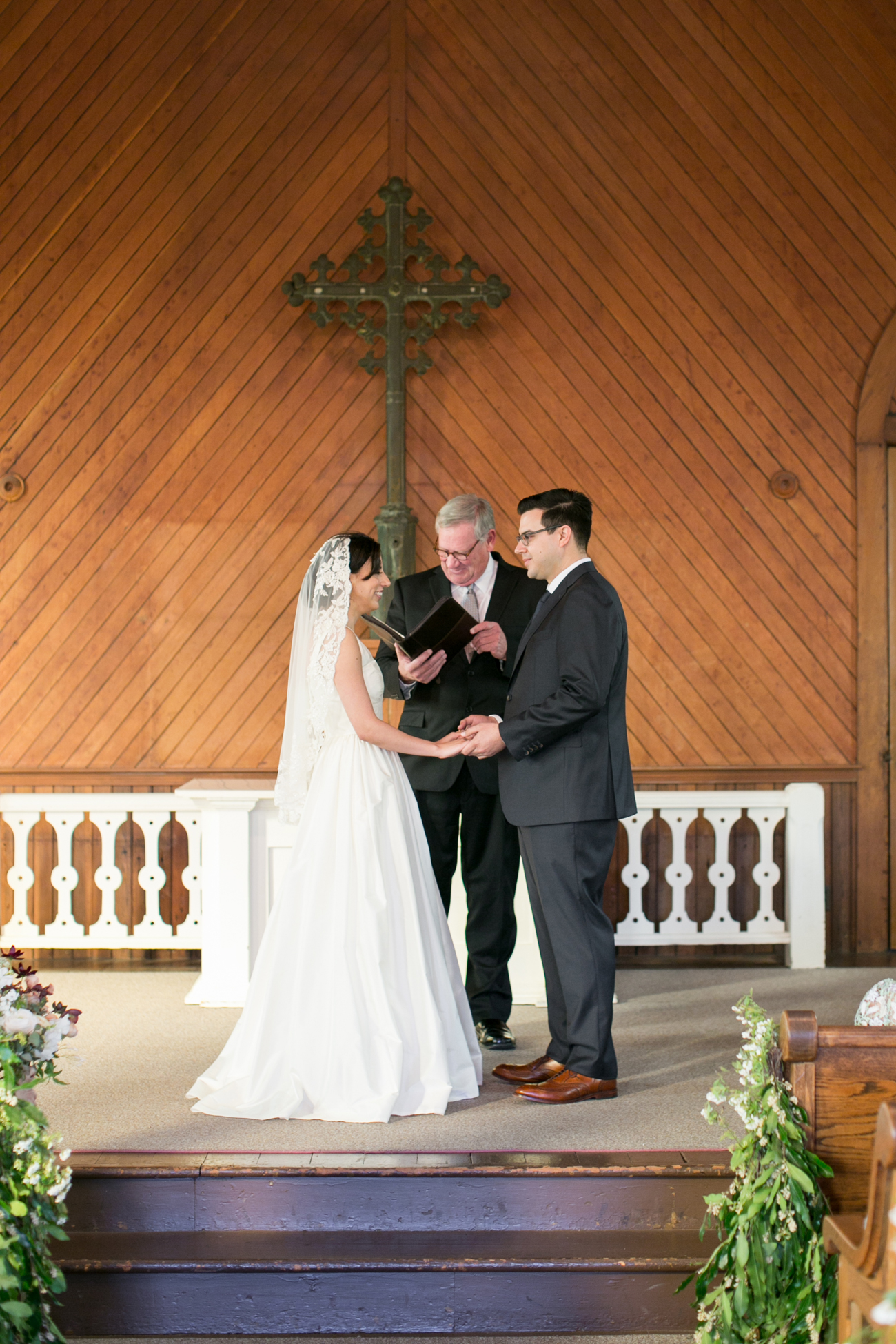 bride and groom hold hands during wedding ceremony