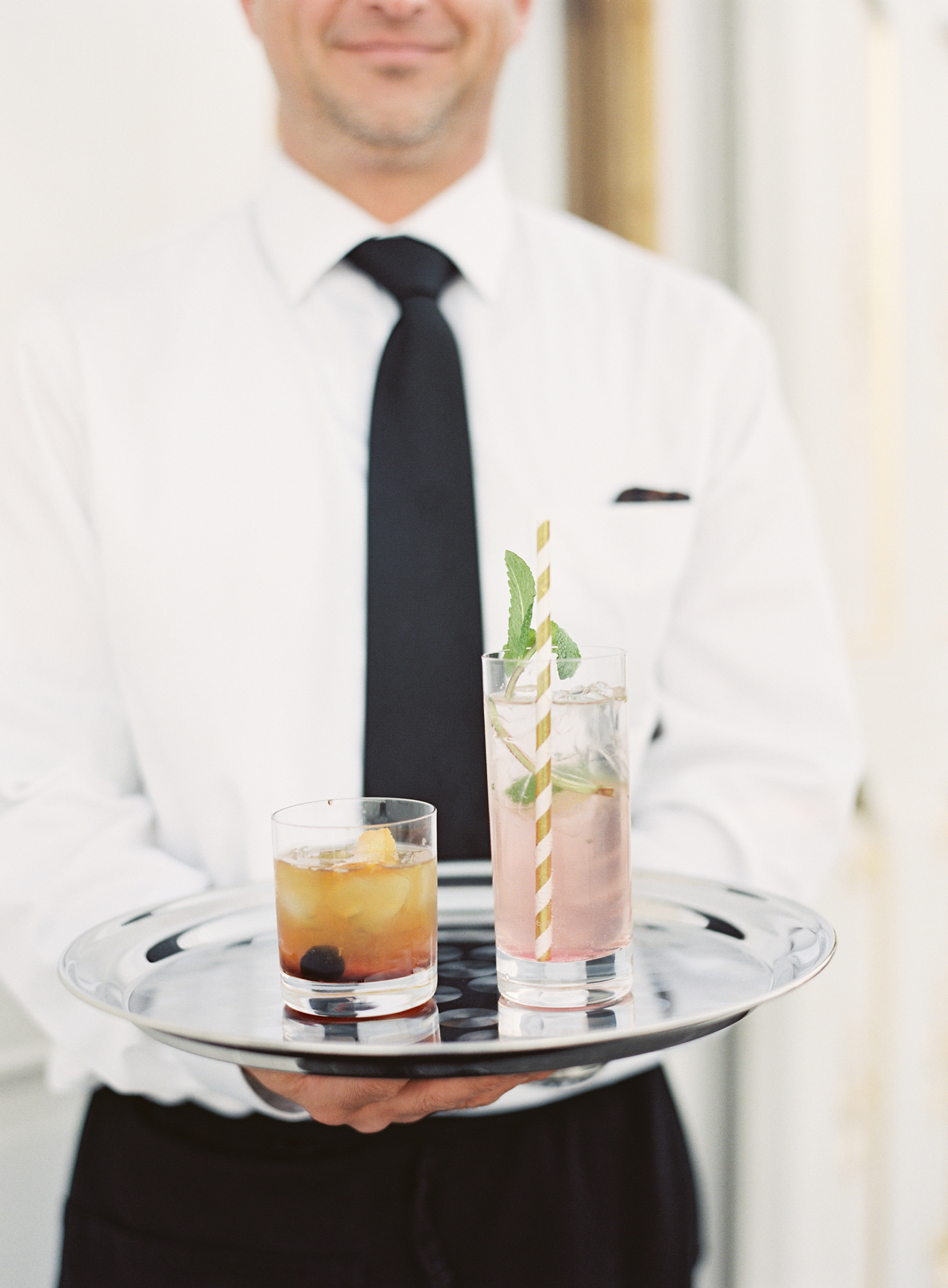 signature cocktails on serving tray held by waiter