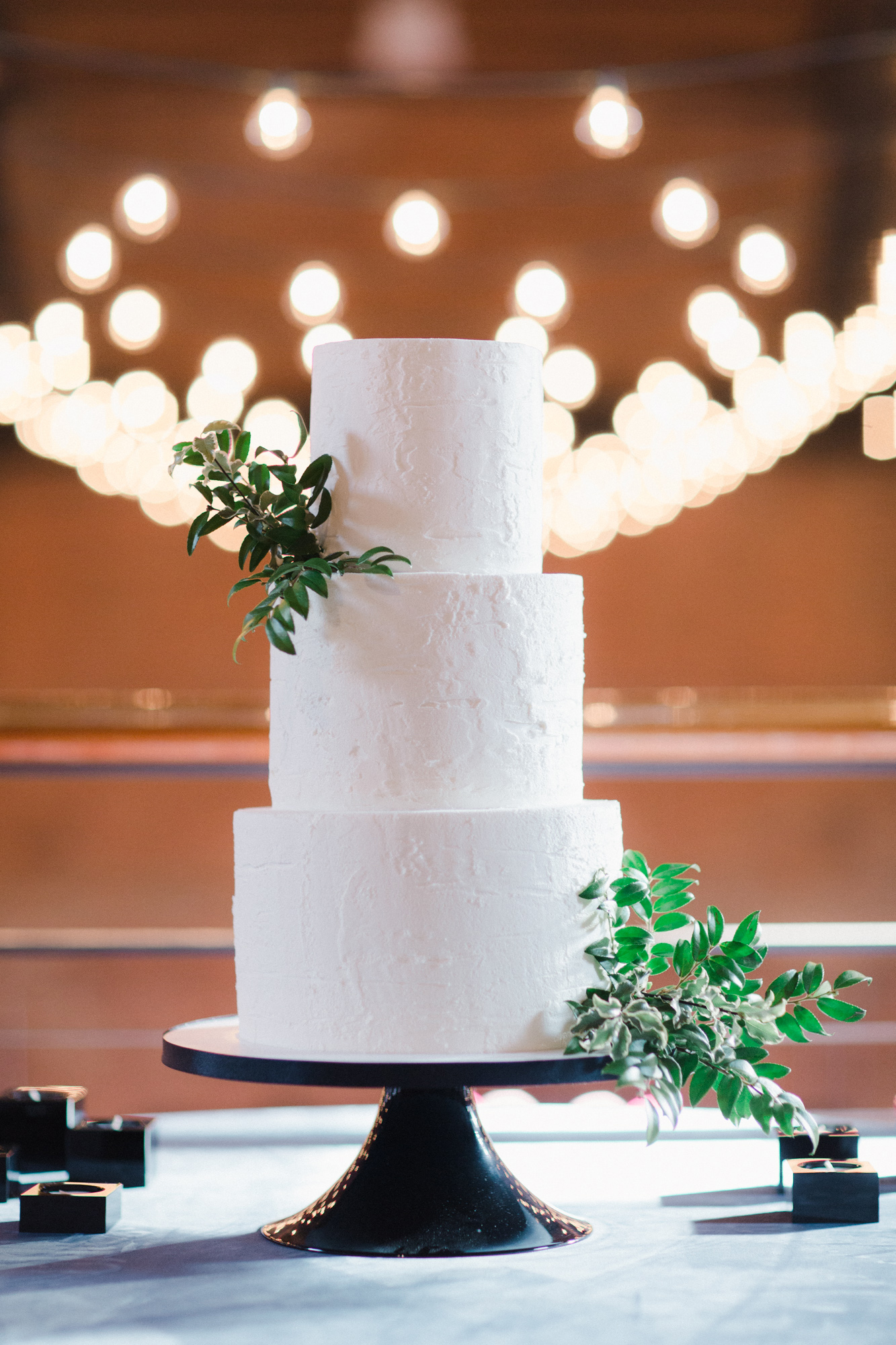 white wedding three tier cake with greenery