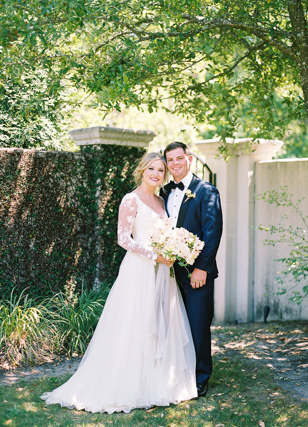 bride and groom posing in front of wall of greenery