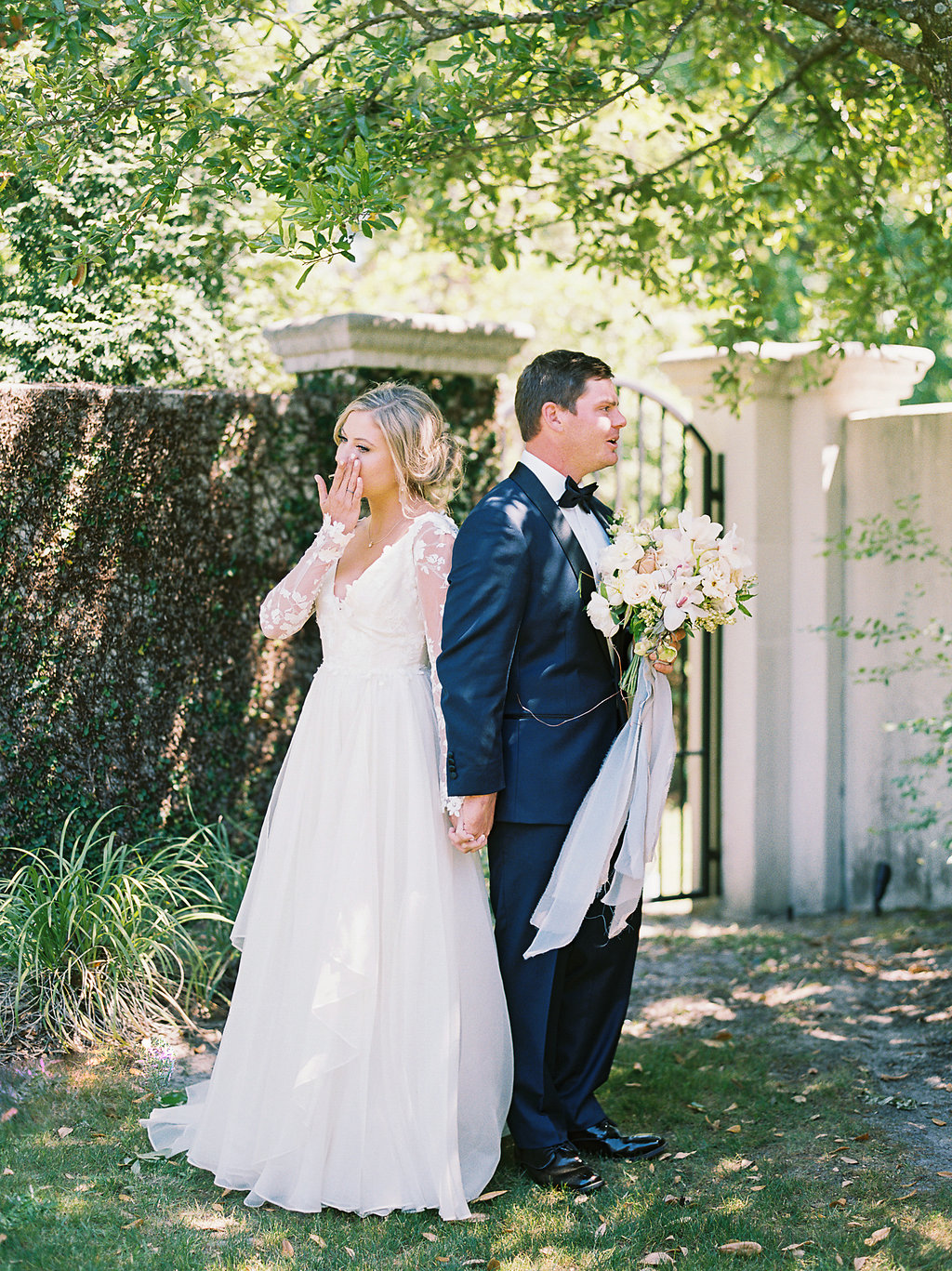 bride and groom sharing tearful first look in front of wall of greenery