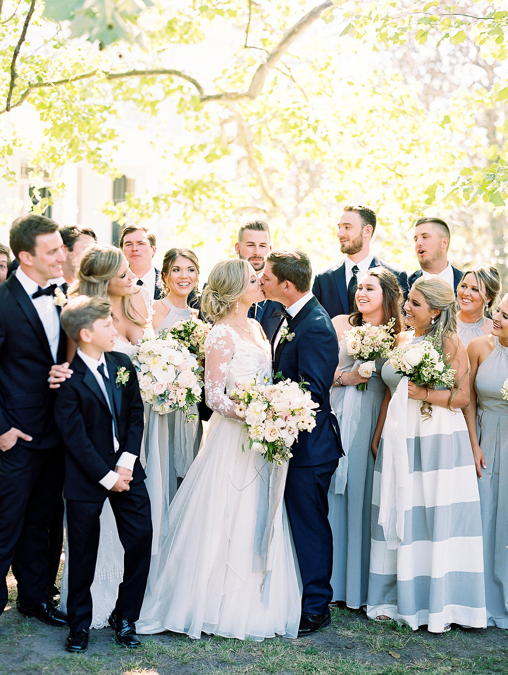 bride and groom kissing in front of wedding party