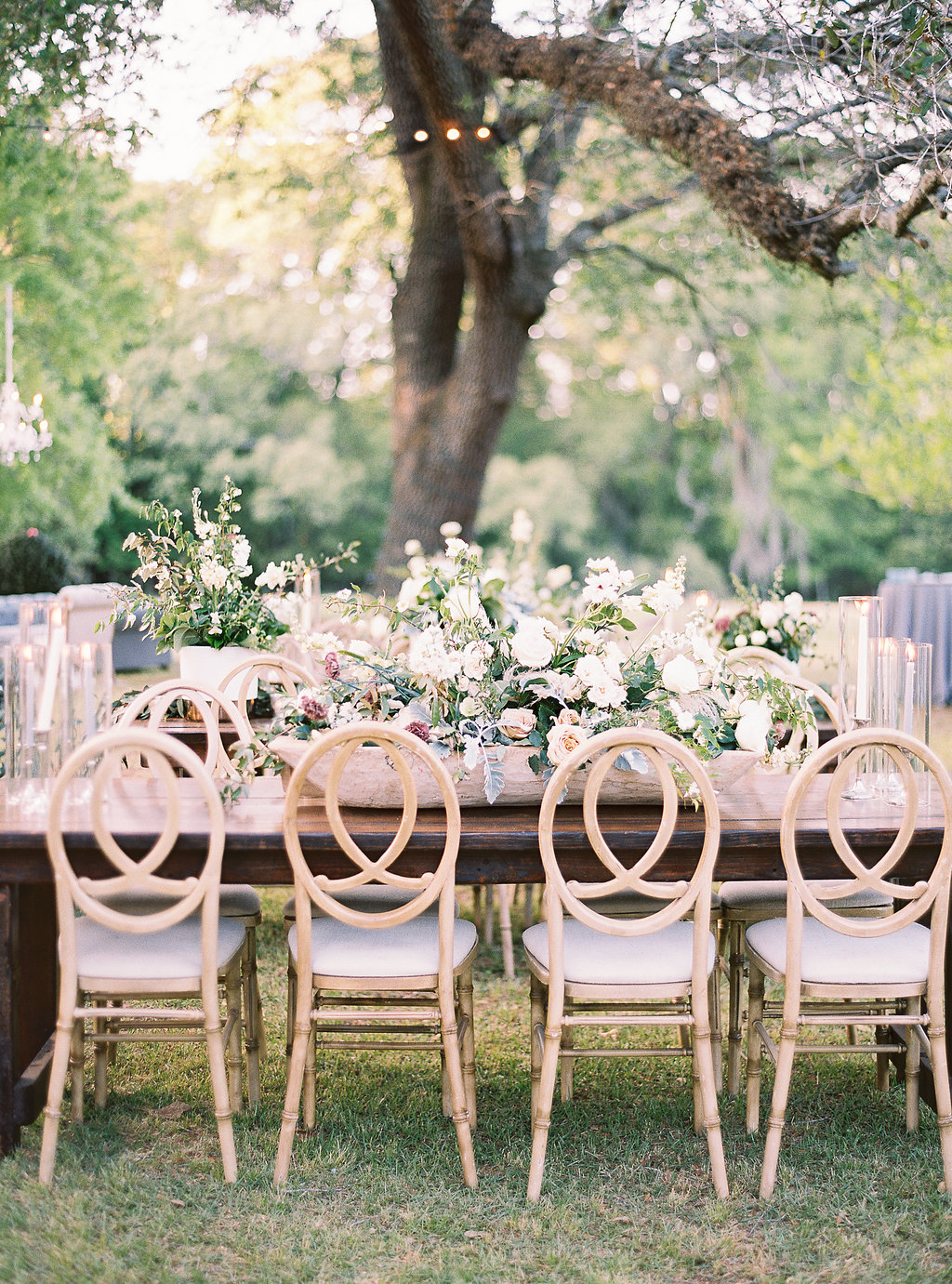 outdoor wedding reception table set up with neutral and green floral arrangements