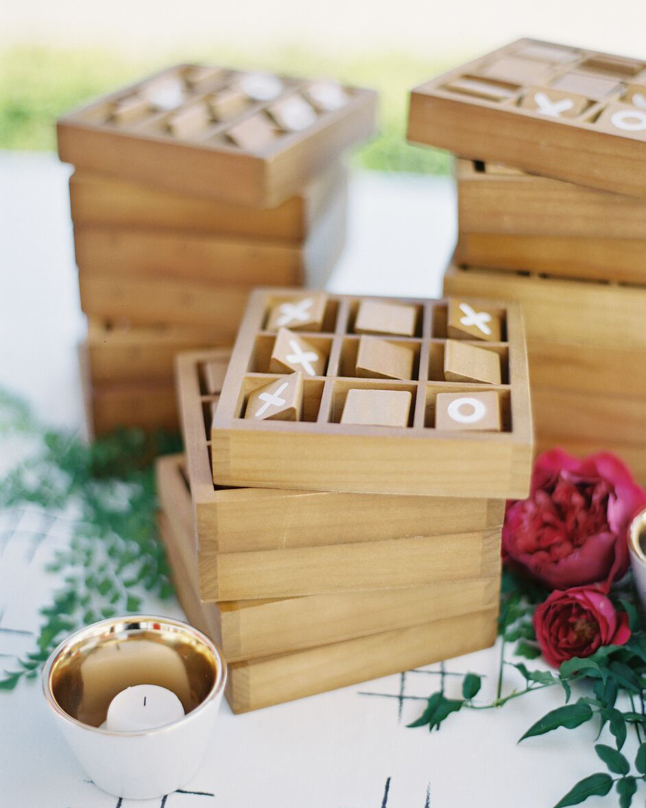 stack of tic-tac-toe wood games next to roses