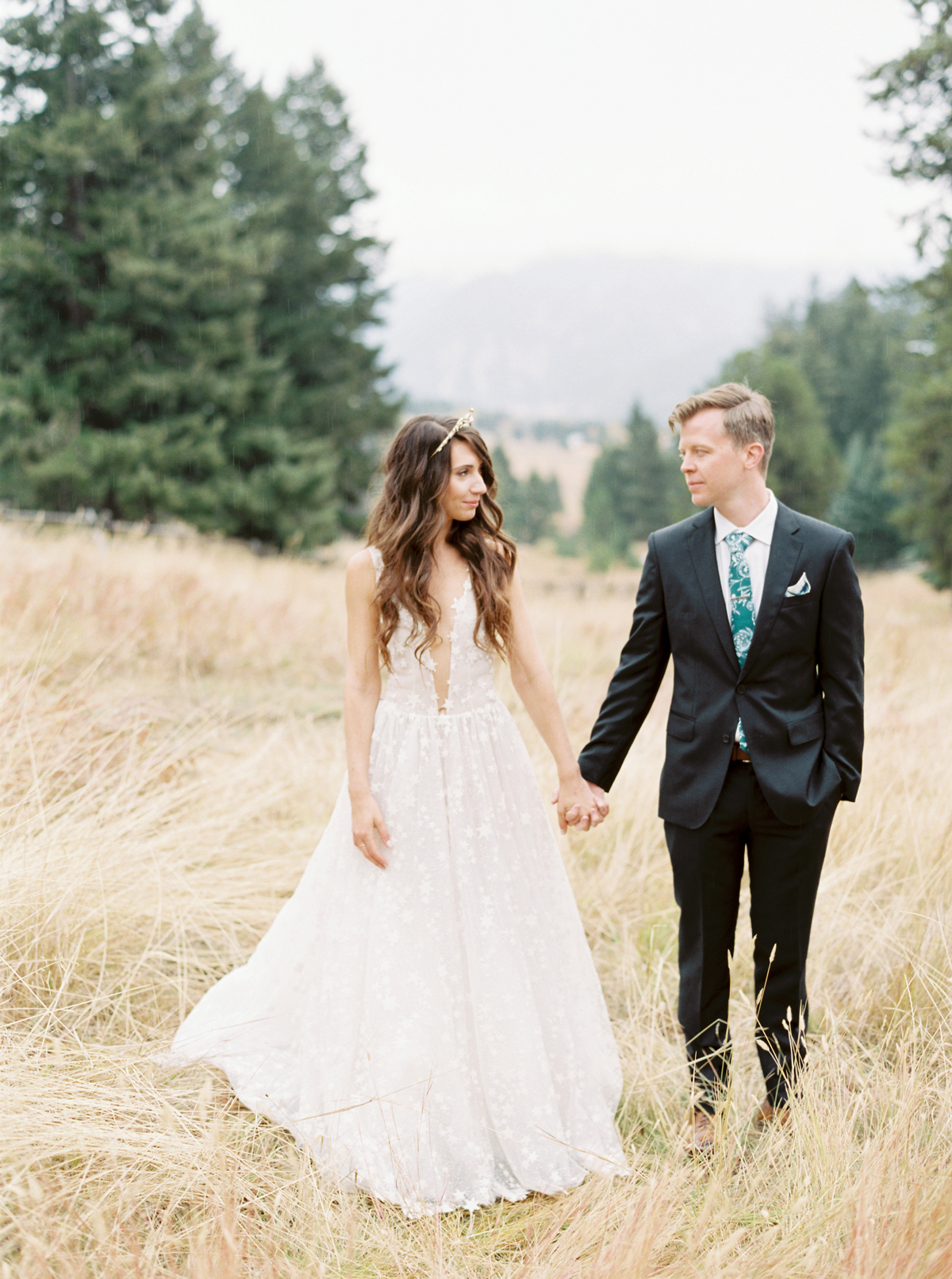 bride and groom holding hands in field