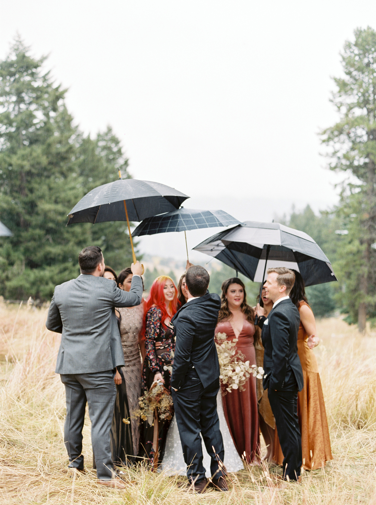 wedding party holding umbrellas