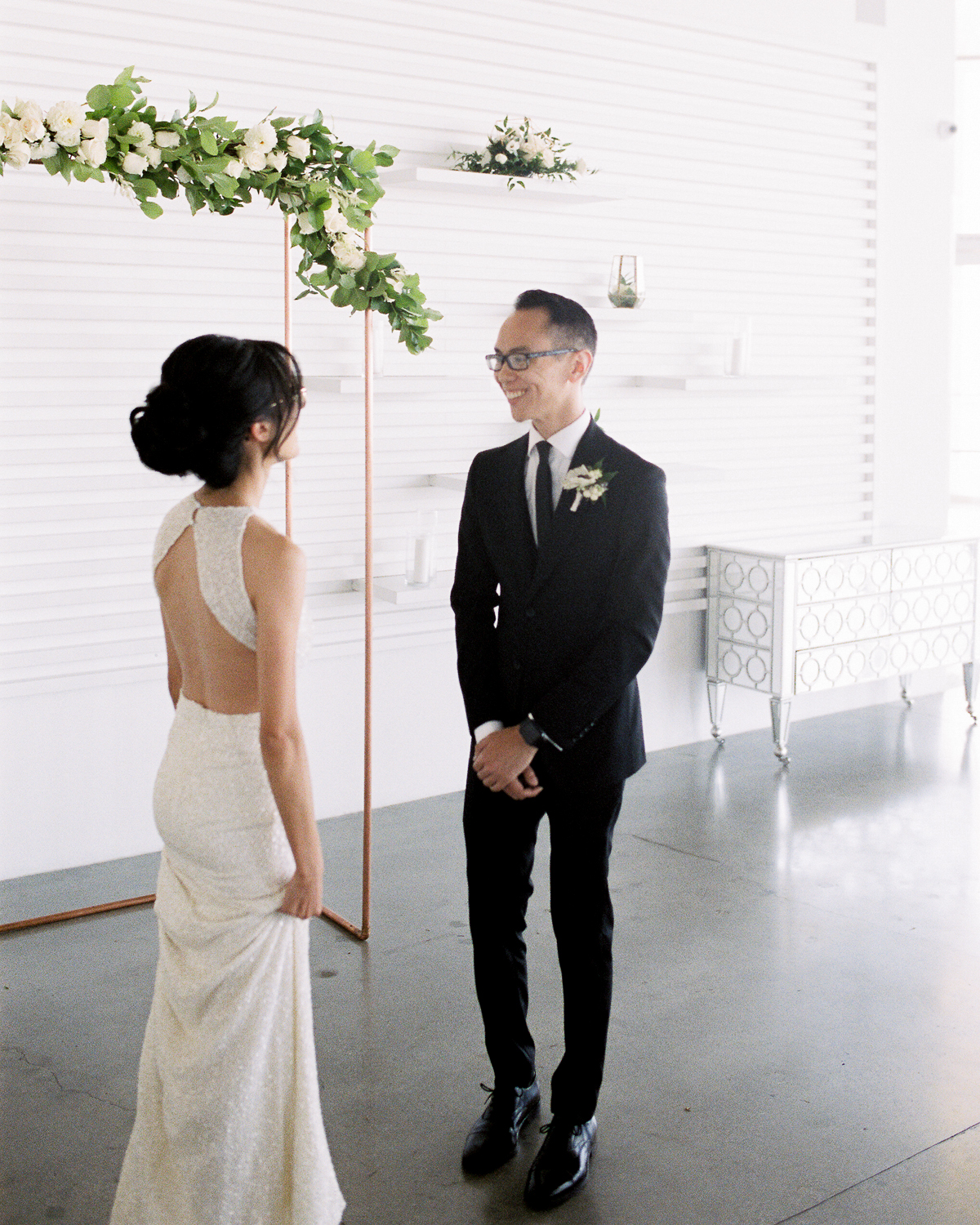 wedding couple first look in front of brass arch