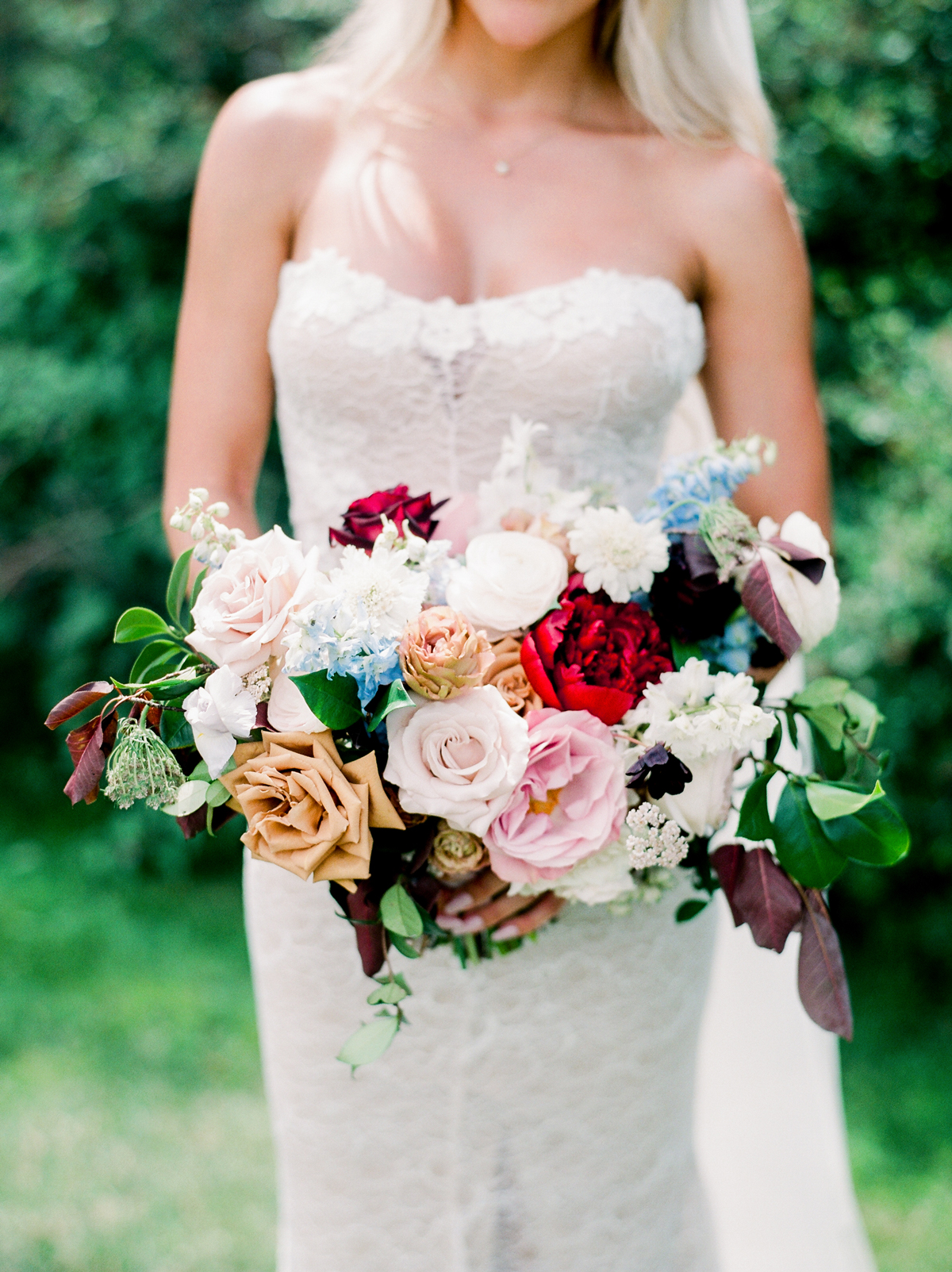 bride holding bouquet with multi-colored roses