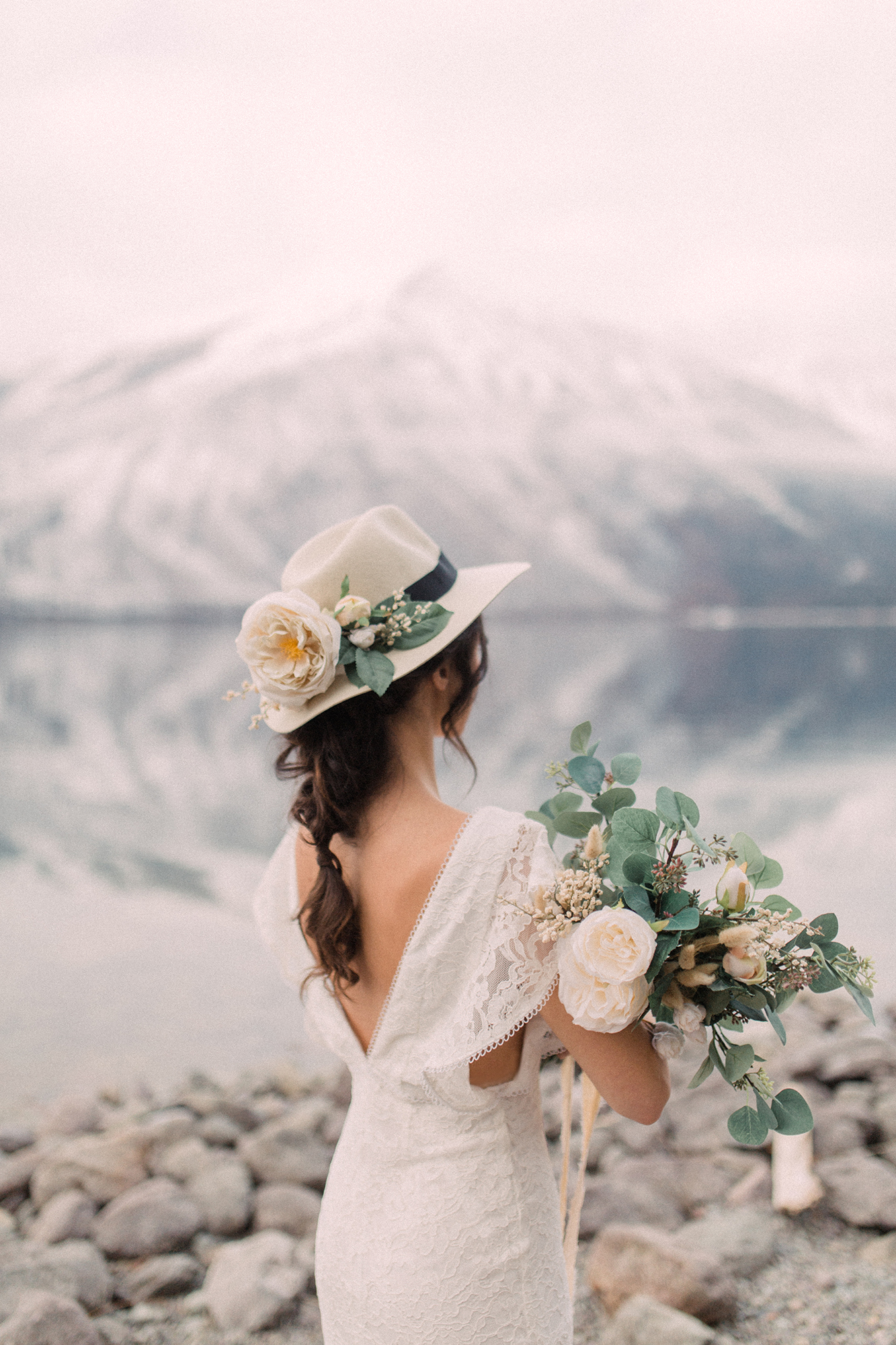 bride wearing hat with black ribbon and flowers