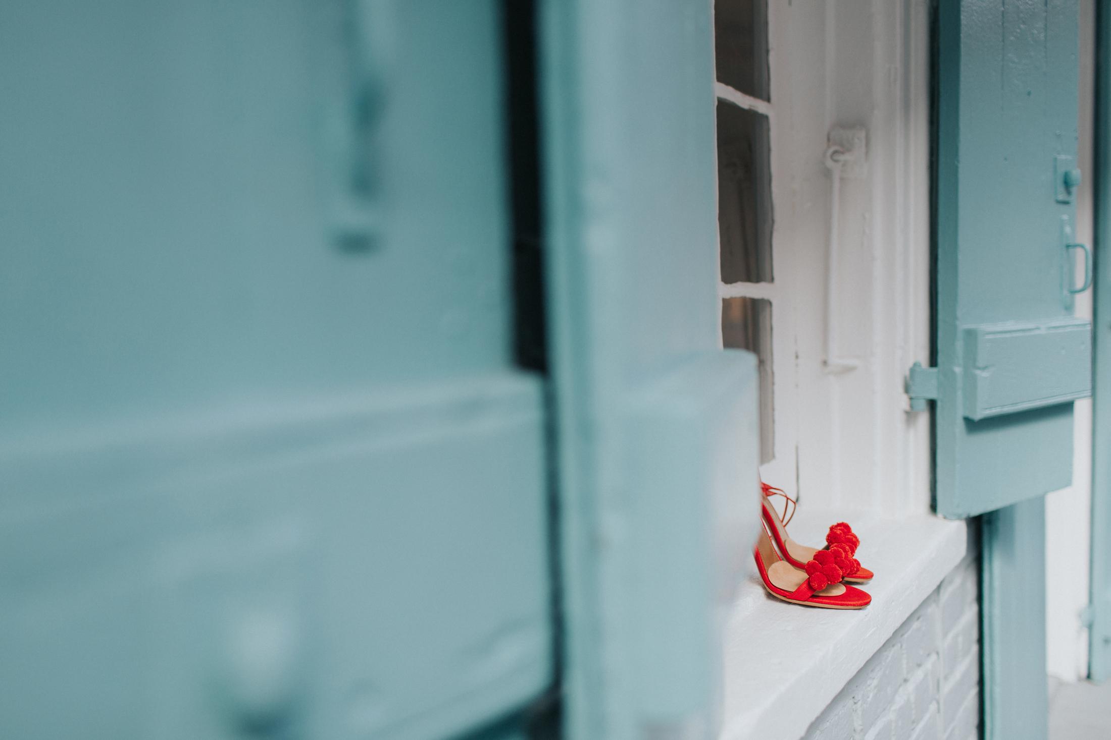red pom pom sandals on windowsill