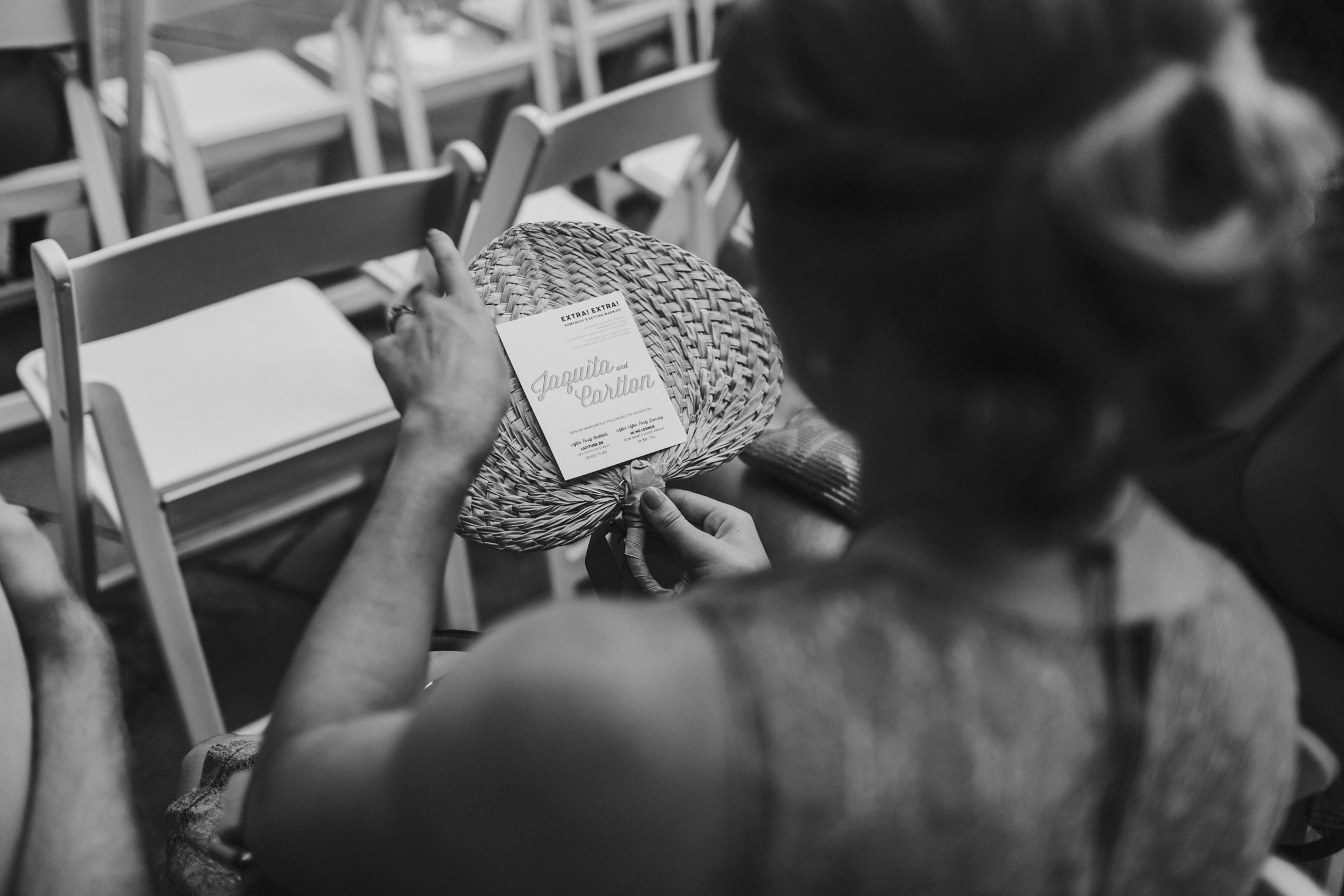 wedding guest holding raffia fan with attached program