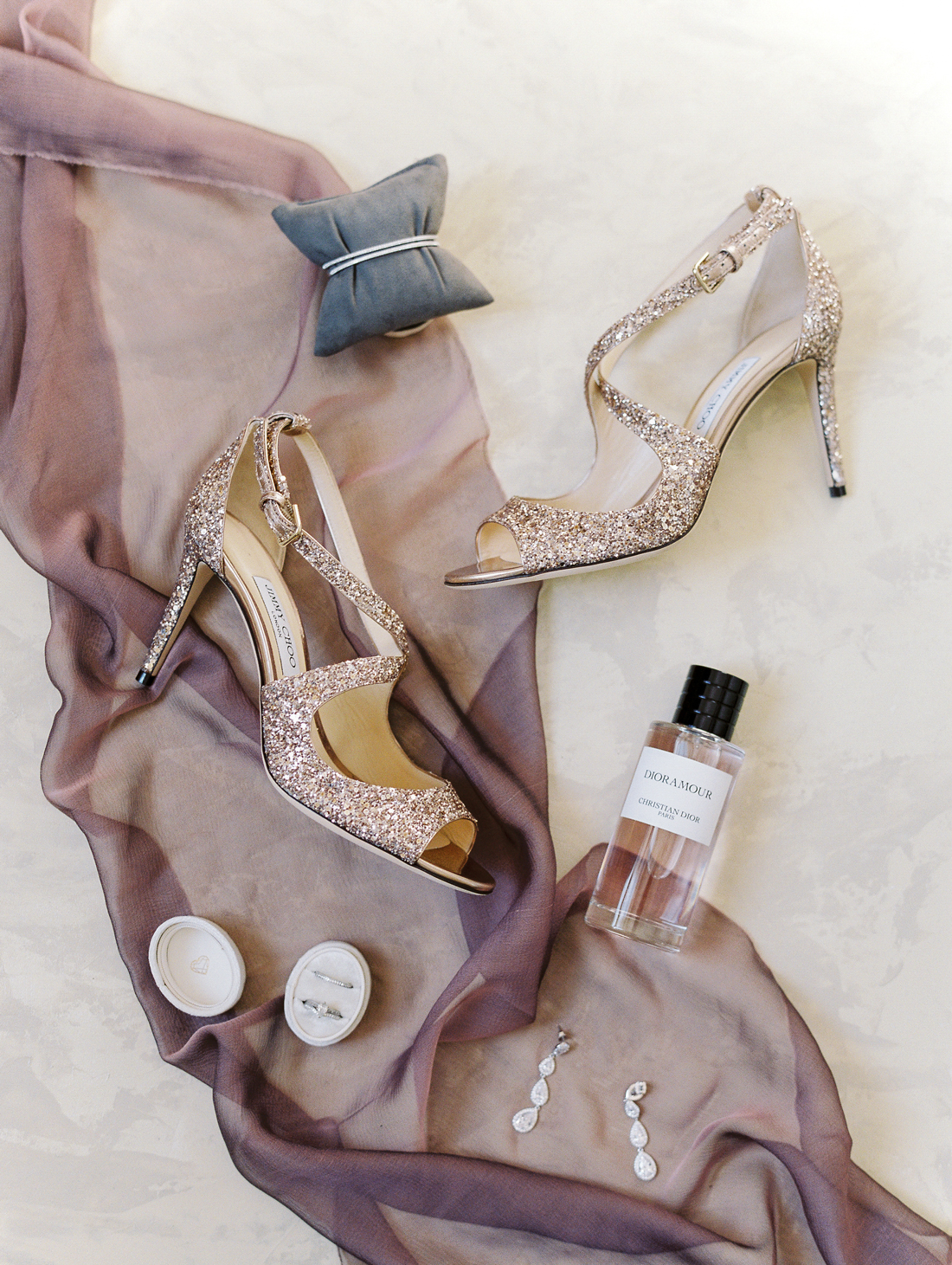 champagne colored heels, diamond earrings, perfume, and other bridal accessories