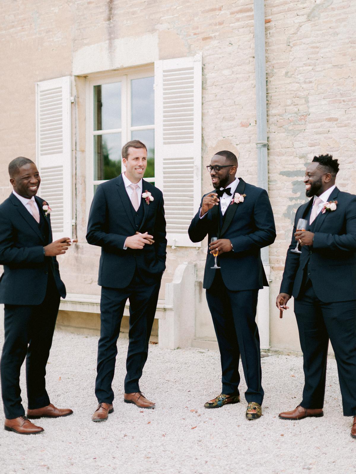 groom standing with groomsmen before wedding