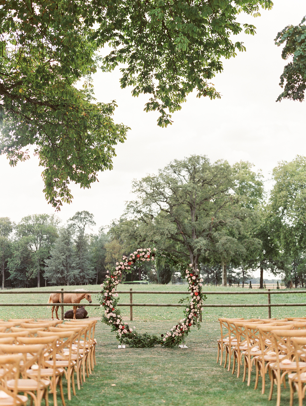 circular floral alter outdoors in front of horse pasture