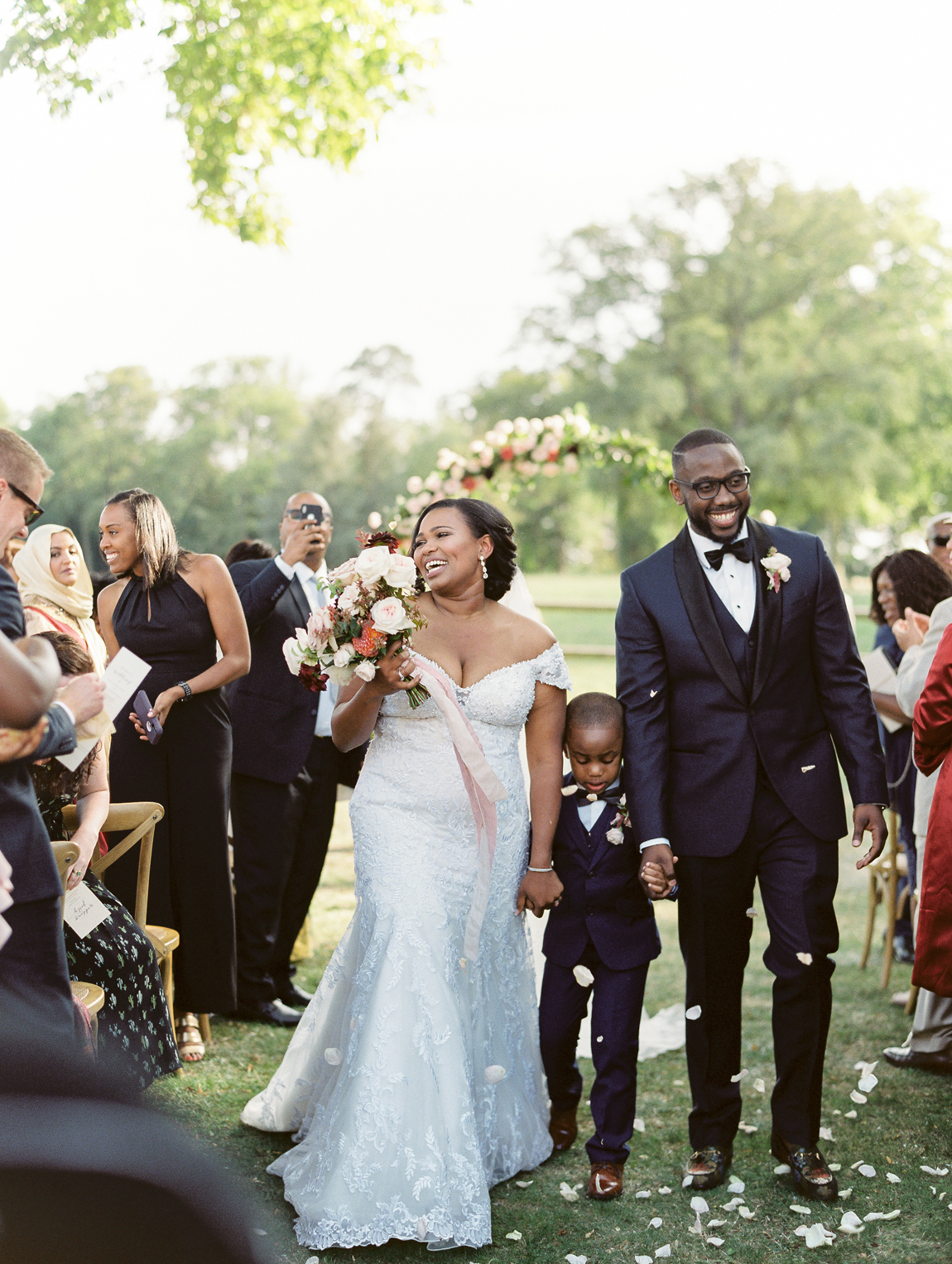 bride and groom with son during wedding recessional