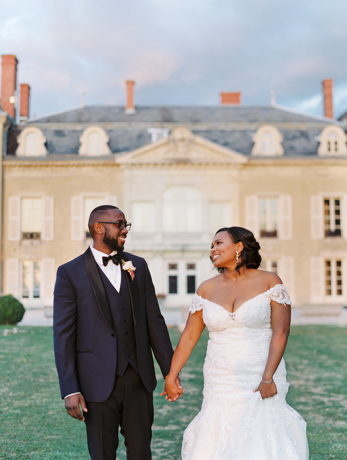 bride and groom holding hands outside wedding venue