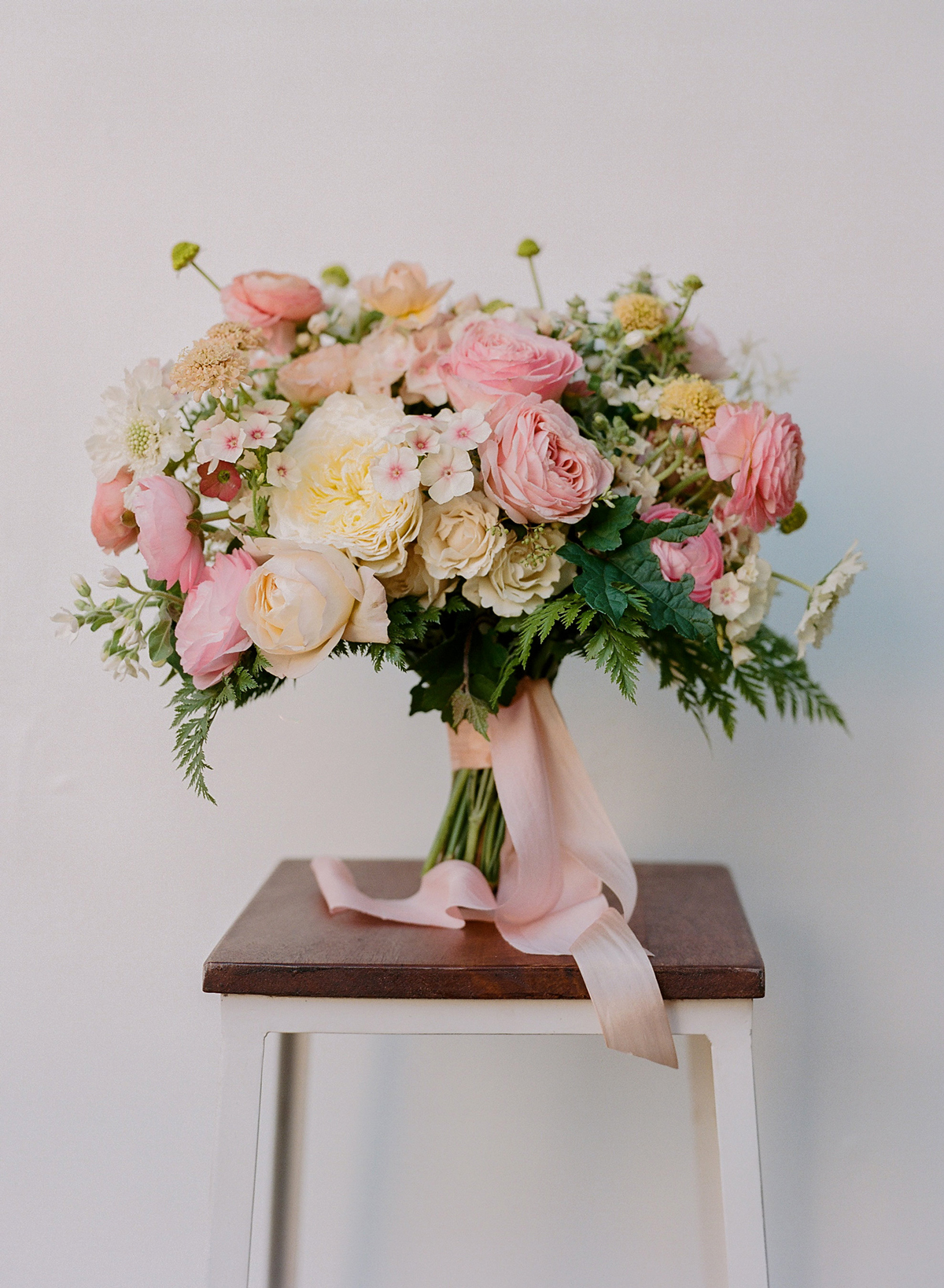 bouquet of white and pink roses with geranium and fern foliage