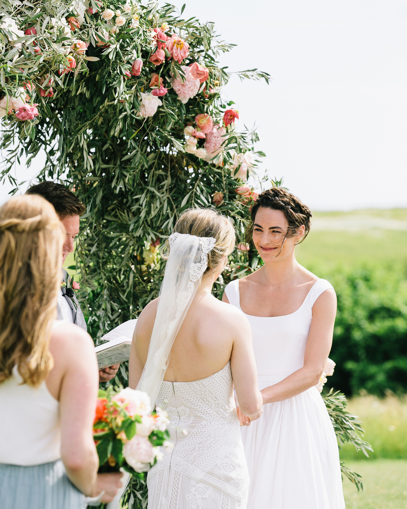 brides stand under floral wedding arch during ceremony