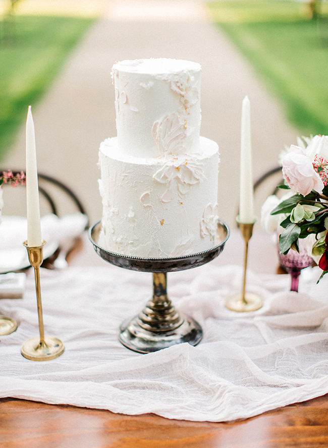 two tiered white frosted wedding cake with gold metallic accents