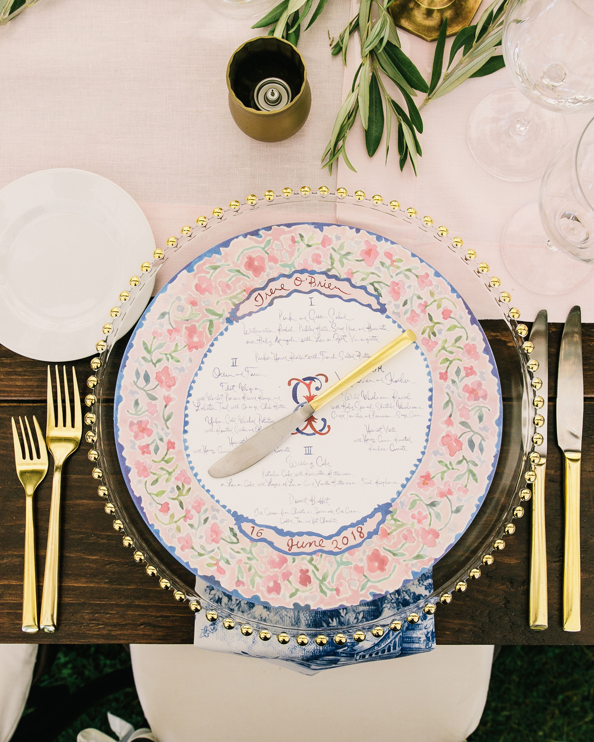 table settings featuring pink linens, blue candles, and gold dishware
