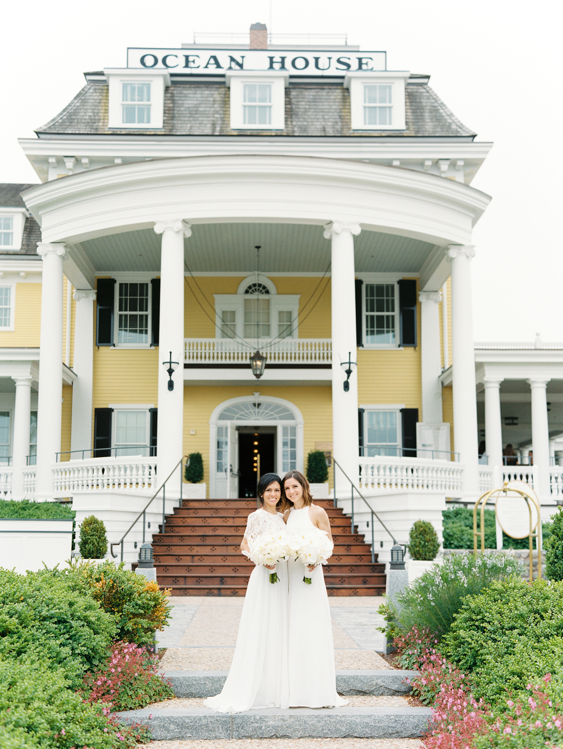brides stand outside pale yellow ocean house with white pillars