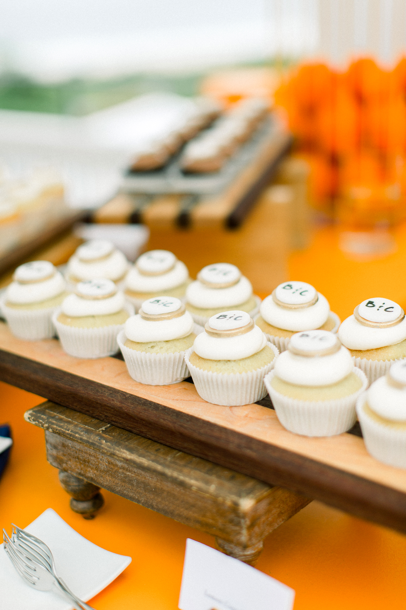 monogramed white frosted cupcakes on orange tabletop