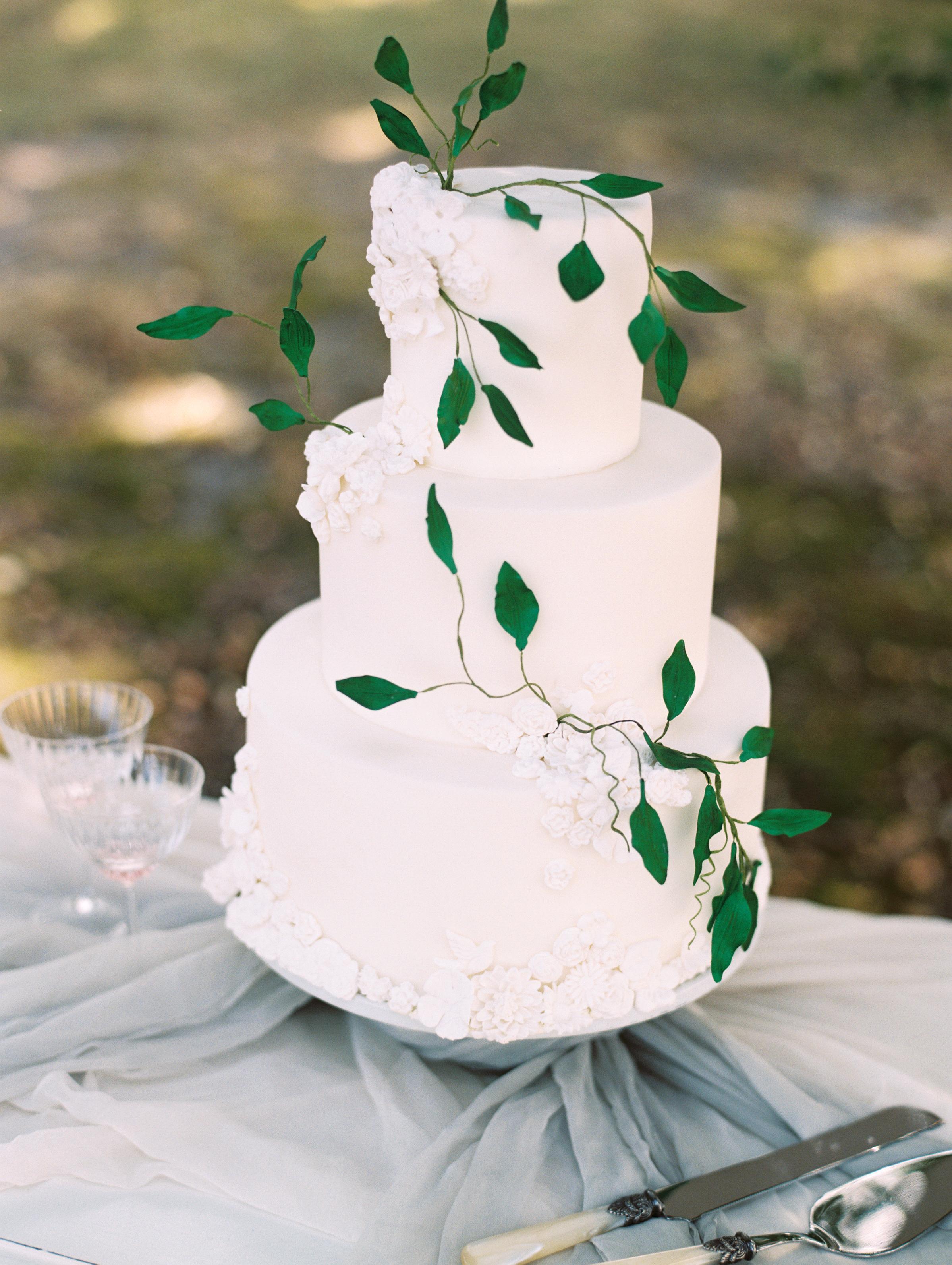 vanilla wedding cake with greenery vine