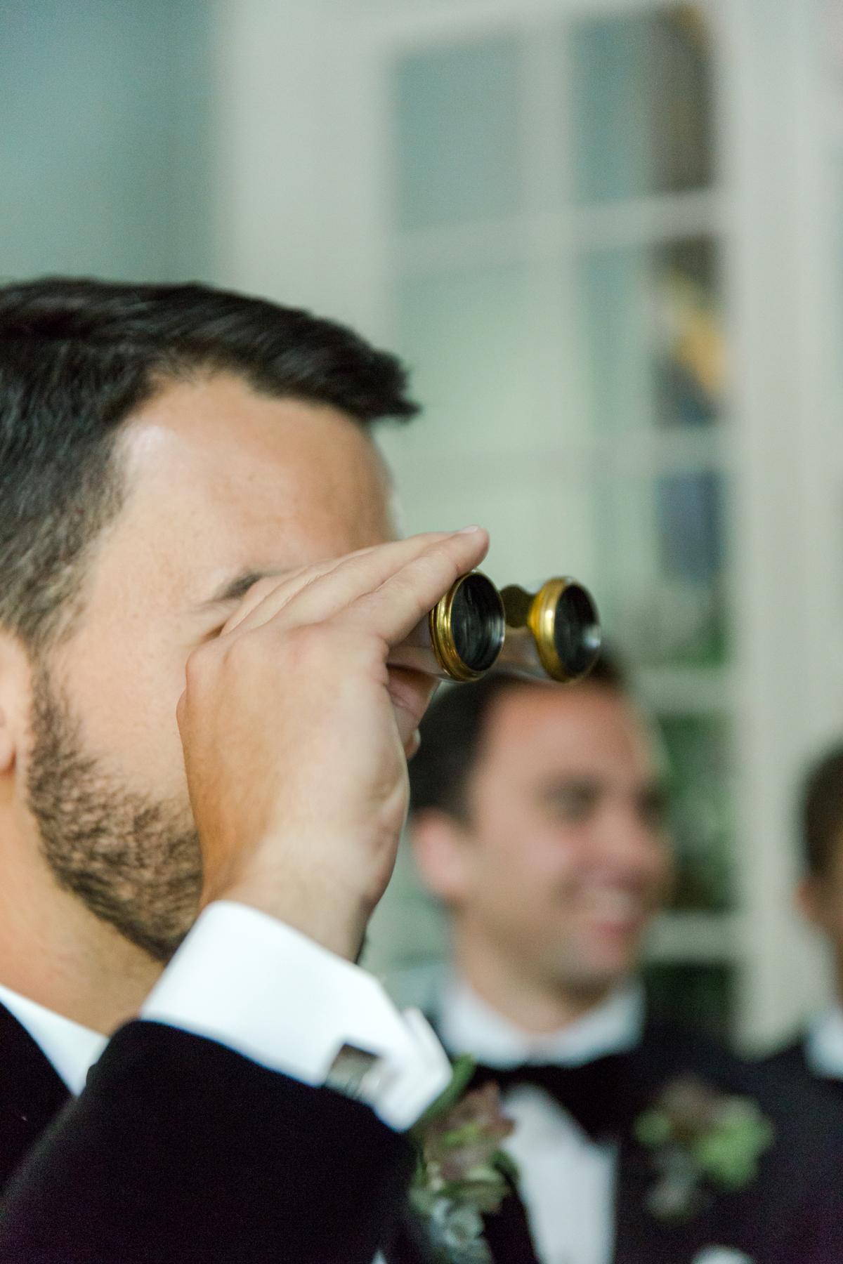 groom viewing bride through vintage binoculars