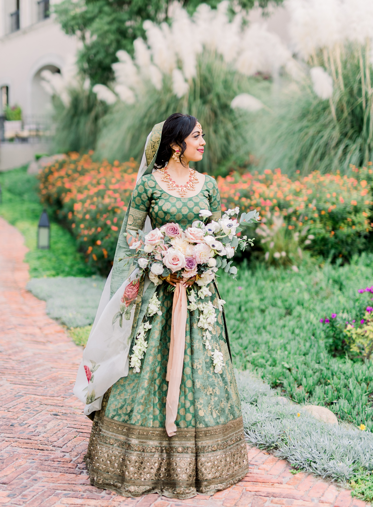 bride wearing green patterned lehenga wedding dress