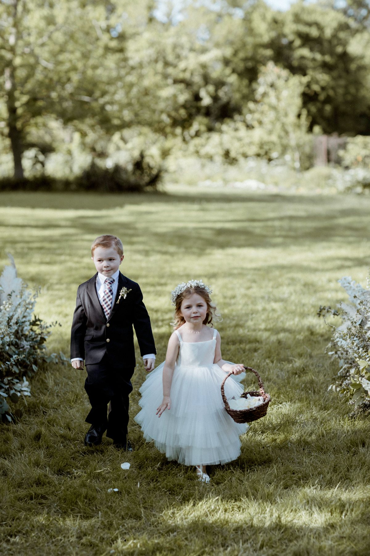 flower girl and ring bearer outside walking on grass