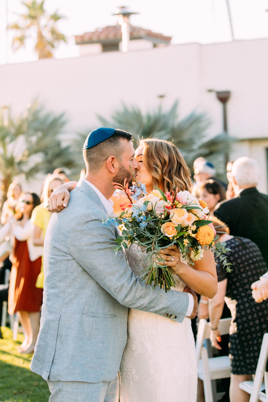 bride groom wedding kiss wearing blue yarmulke
