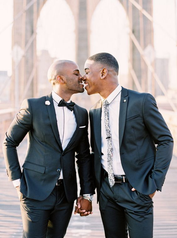grooms wearing black wedding suits with one wearing floral print tie