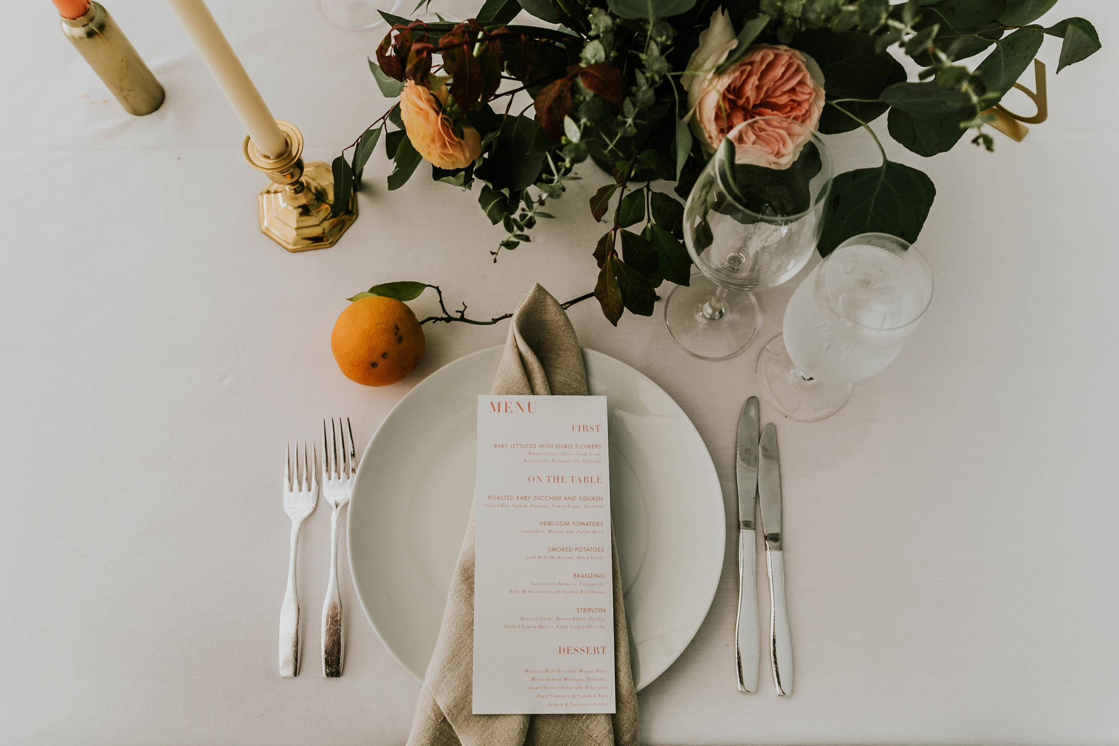 neutral reception place setting decorated with oranges