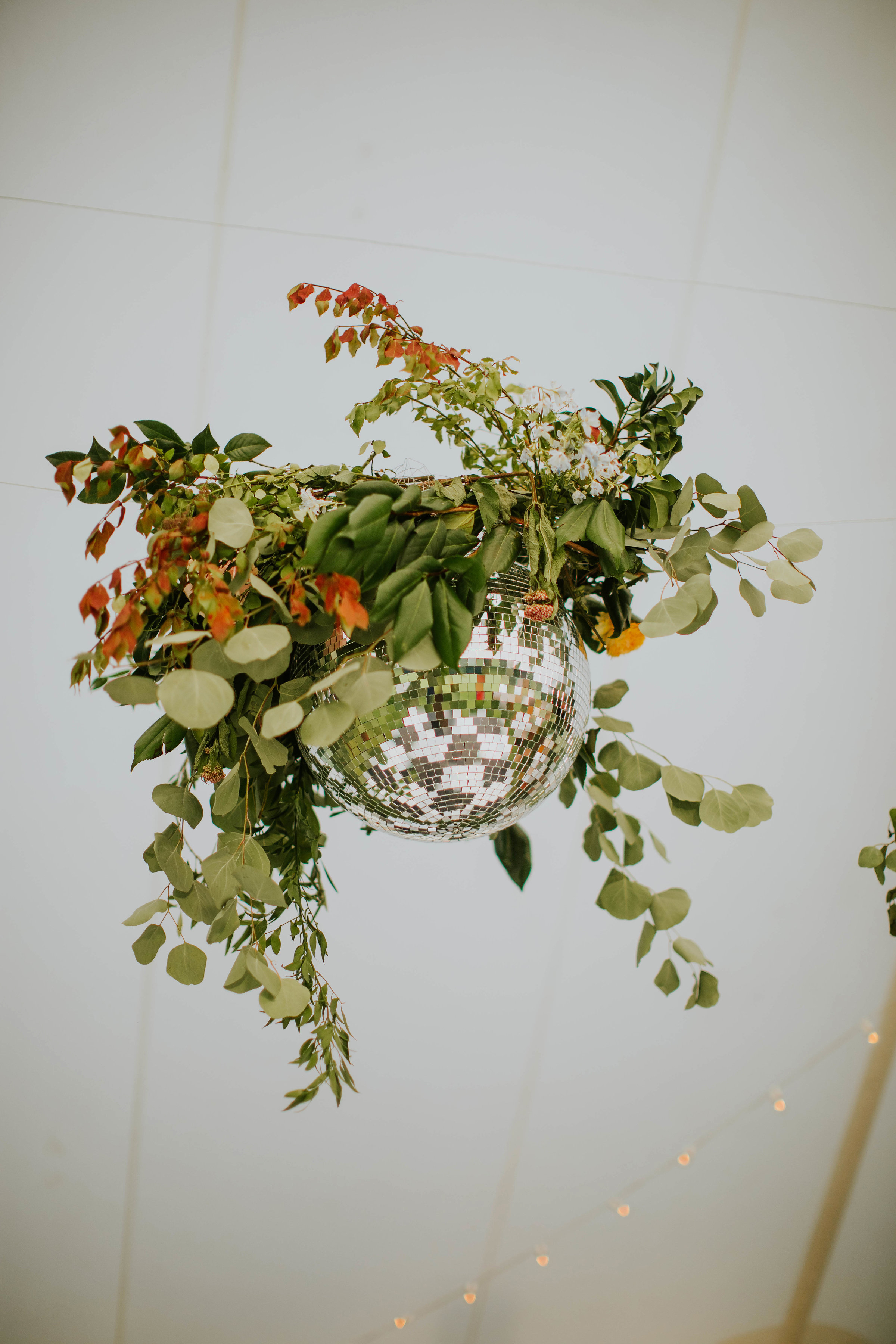 disco ball intertwined with greenery and florals