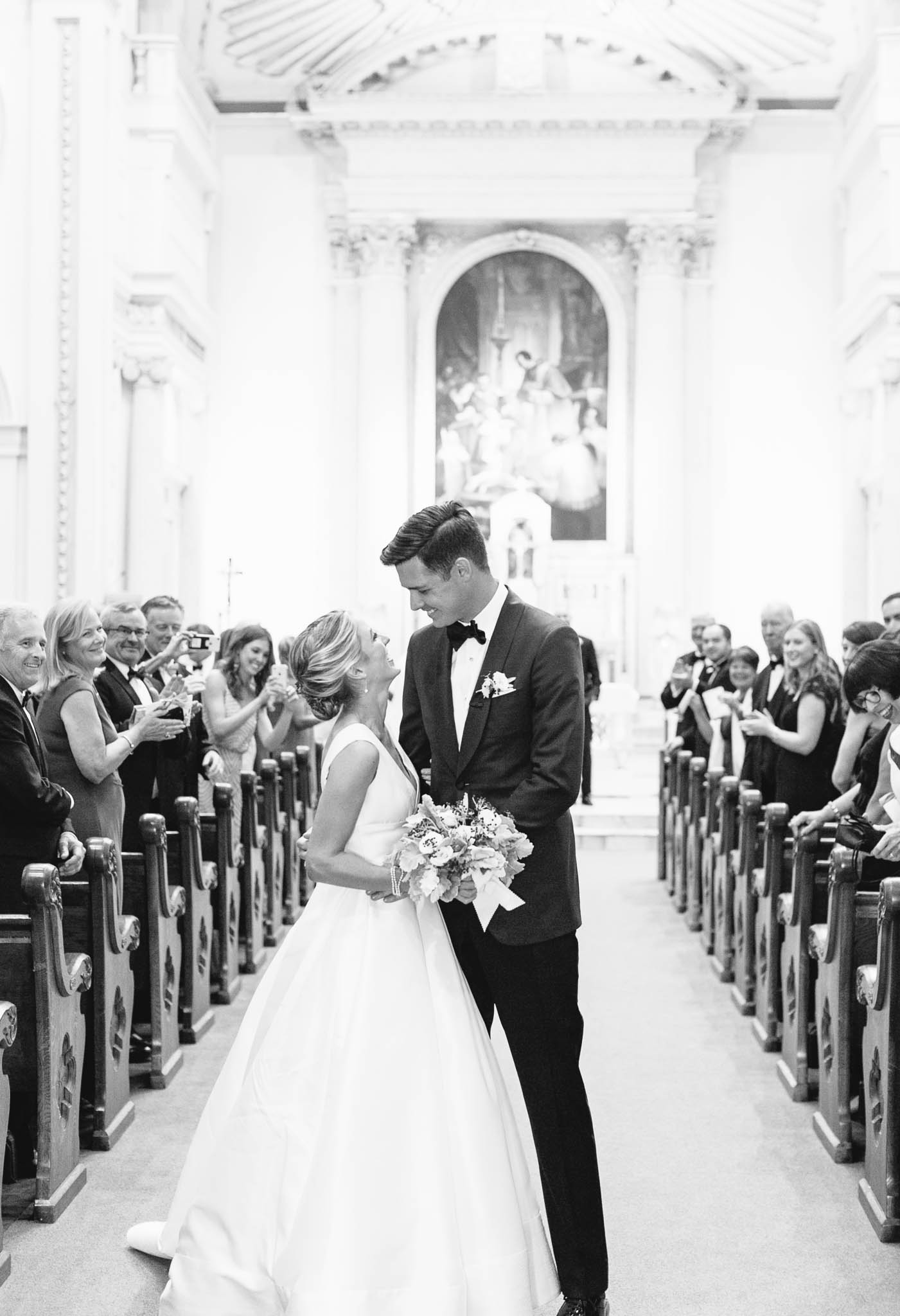 bride and groom standing in church wedding aisle