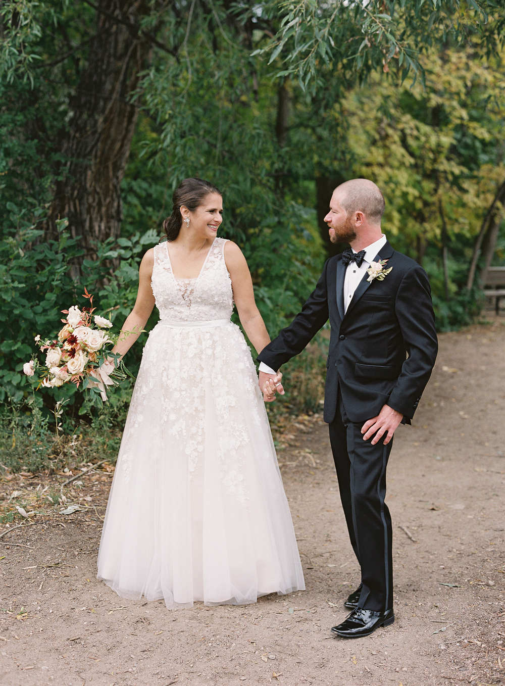 bride and groom holding hands on outdoor pathway