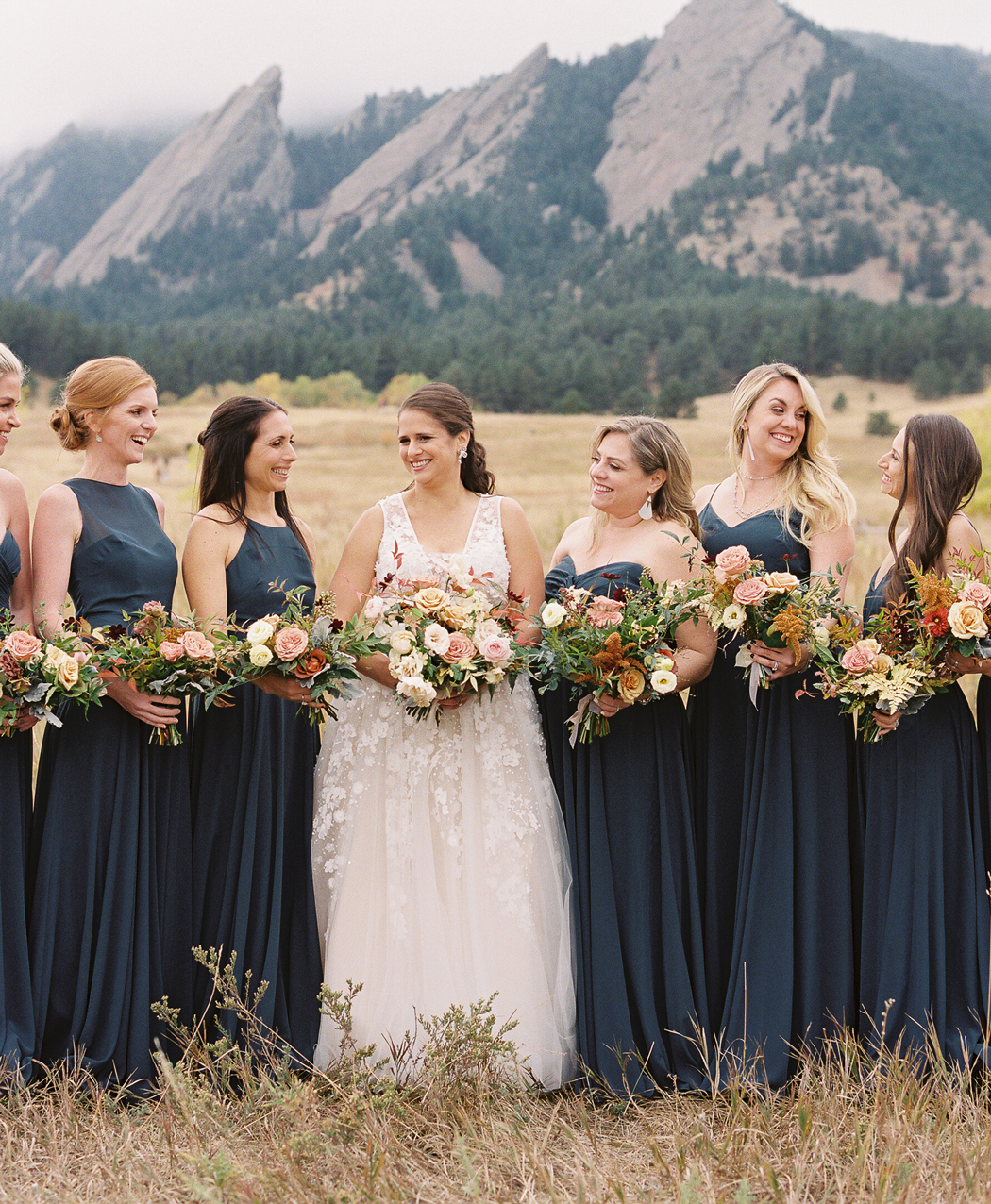 bride surrounded by bridesmaids wearing floor length dark chiffon dresses