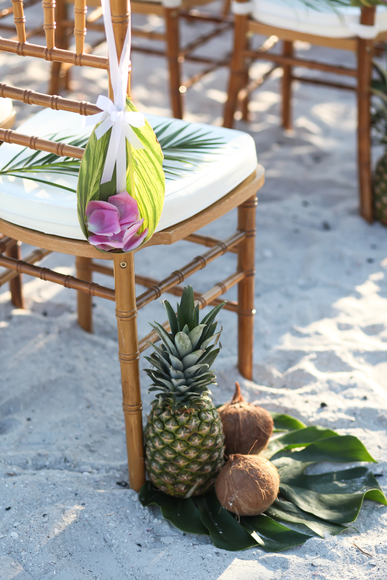 Pineapples, coconuts, and split leaf philodendron leaves aisle decor