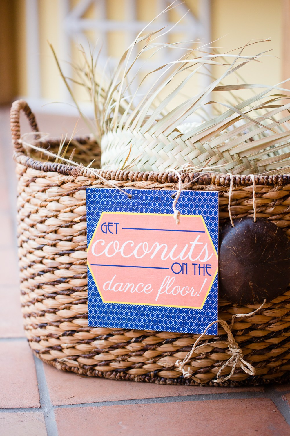 "woven basket with ""Get Coconuts on the Dance Floor!"" sign"