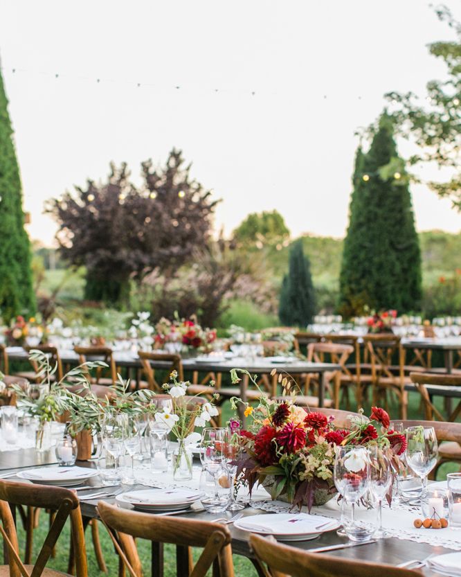 outdoor wedding reception tables with warm floral accents and nearby shrubs