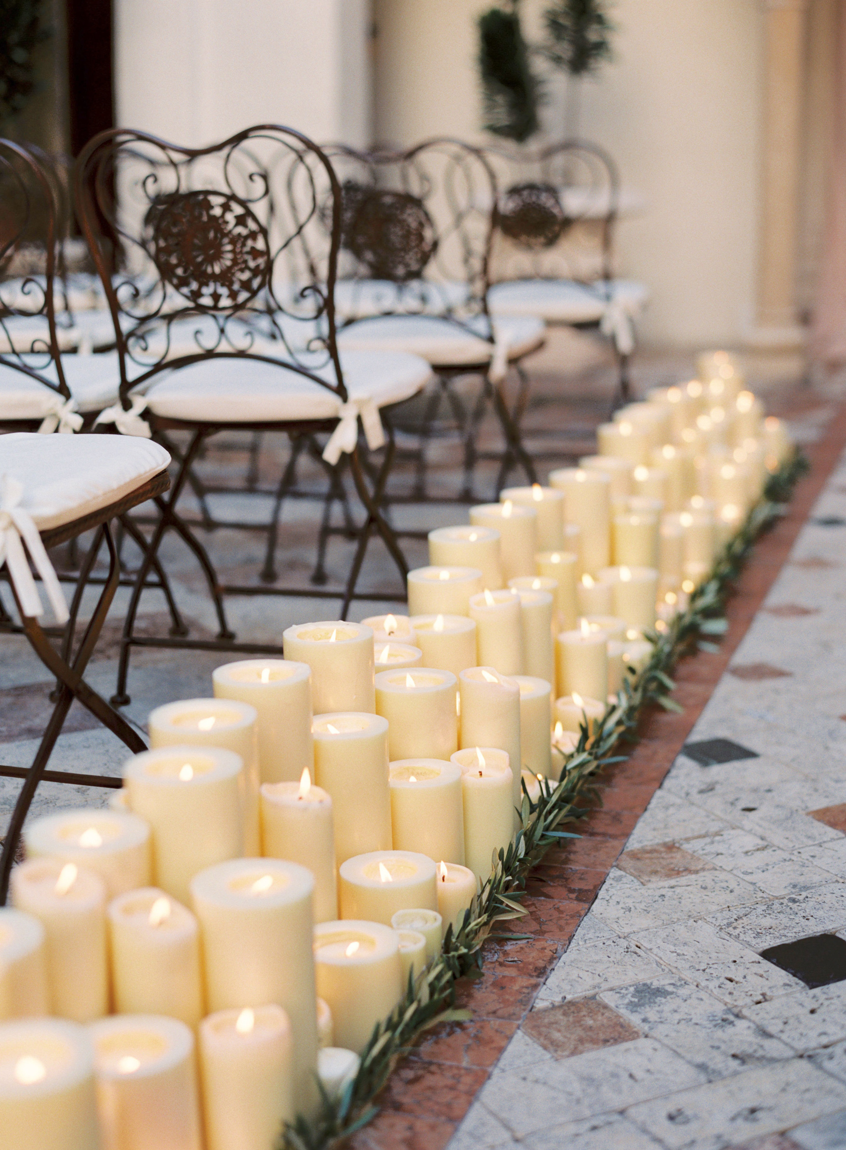 lit pillar candles with greenery lining wedding aisle