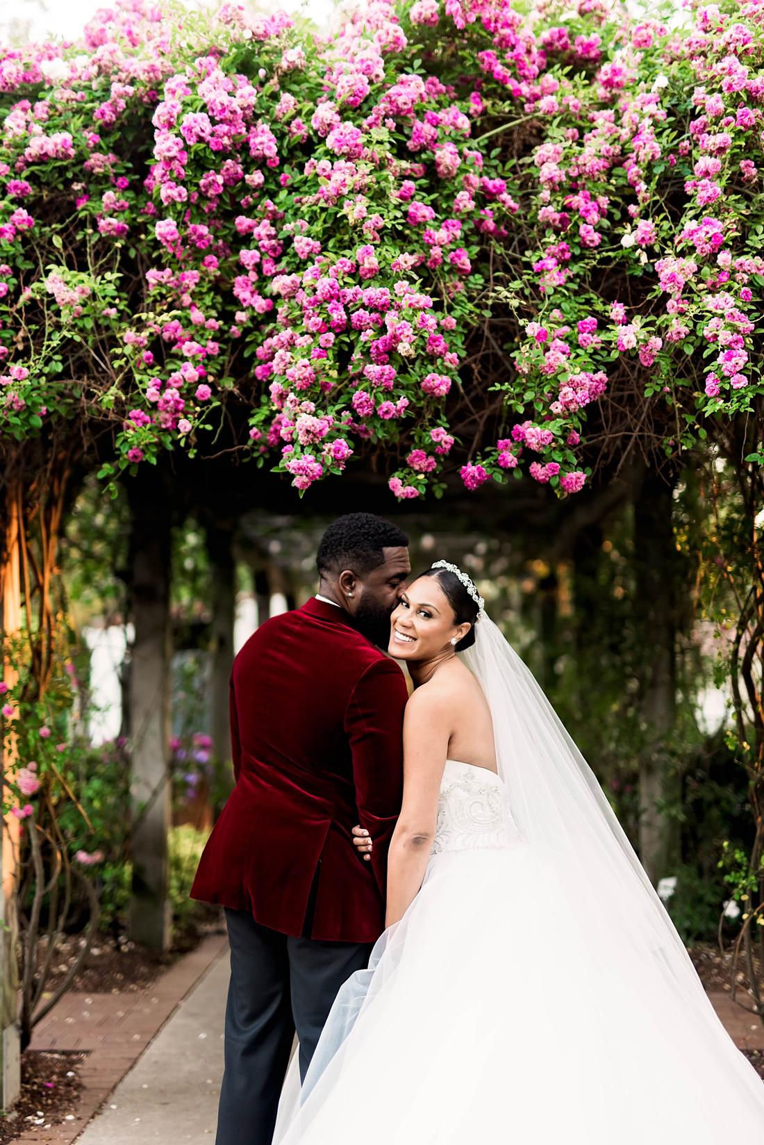 bride and groom pose in botanical garden