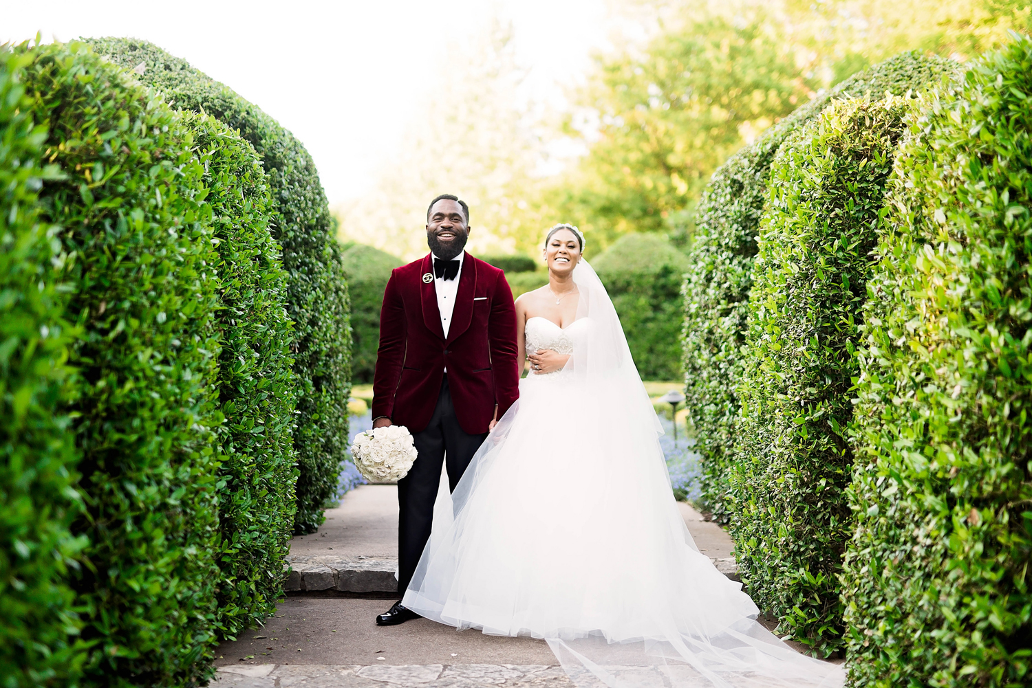bride and groom pose for portrait between shrubs