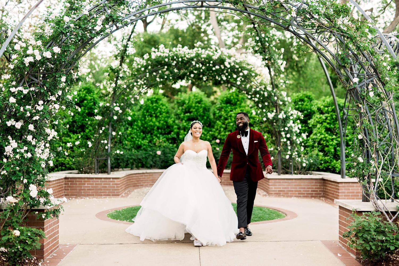 bride and groom walking under garden arch