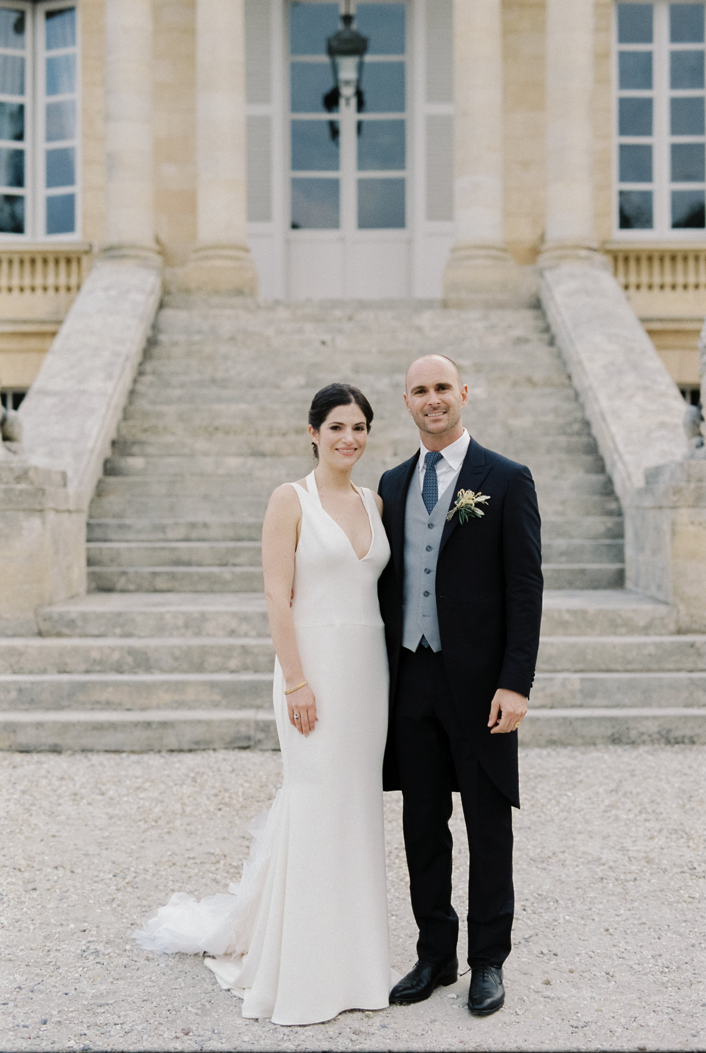 bride and groom pose outside Chateau La Louviere wedding venue