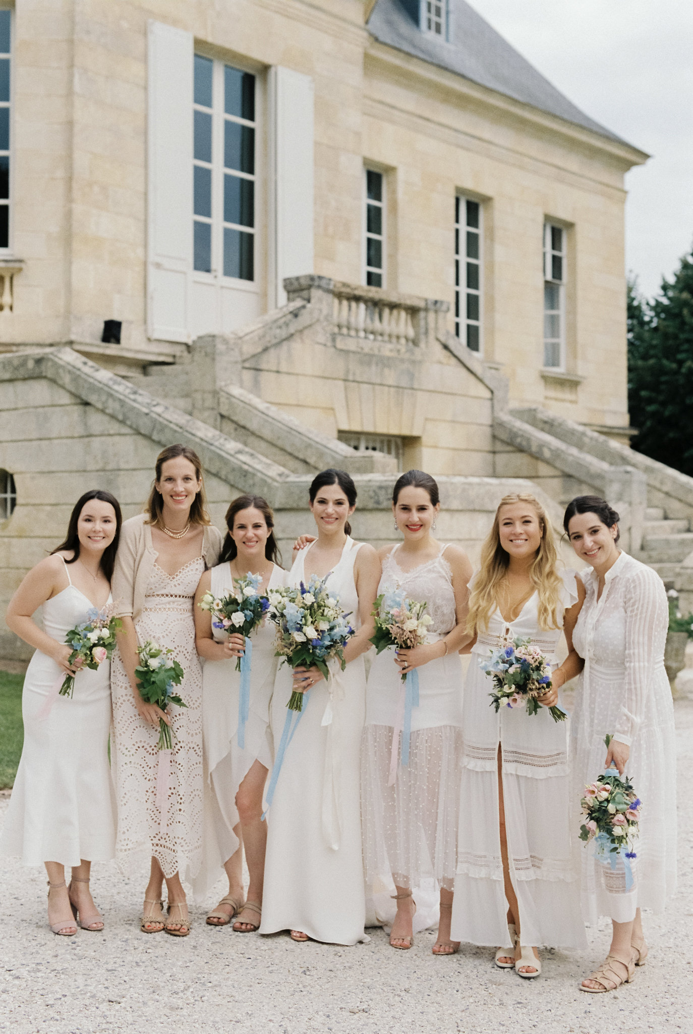 bride with bridesmaids in various white and off white dresses