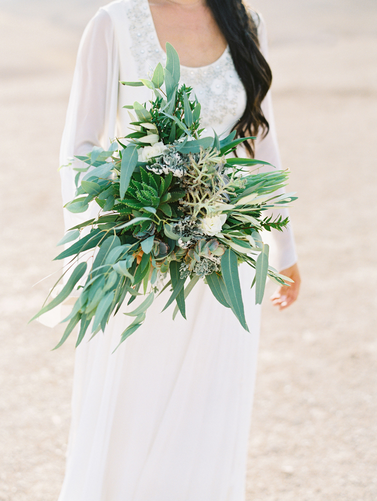 bride holding bouquet made of greenery